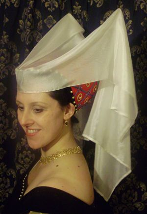 Hennins were all the rage for high-class ladies in the second half of the 1400's. Apparently this style of headdress is called a Butterfly Hennin. It looks bizarre, but I actually think it's more attractive than the Tudor gable hoods that became fashionable in the 1500's.