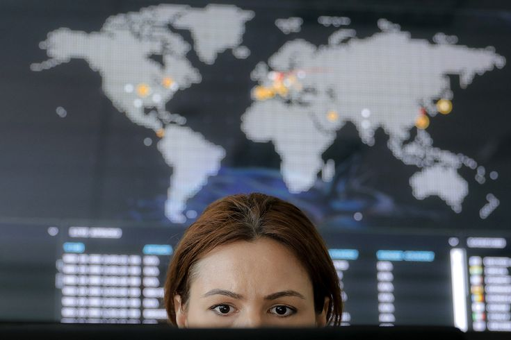 A woman looks at a computer monitor back dropped by a real time cyber-attacks world map, at the headquarters of Bitdefender in Bucharest, Romania, Wednesday, June 28, 2017. (Vadim Ghirda/AP)