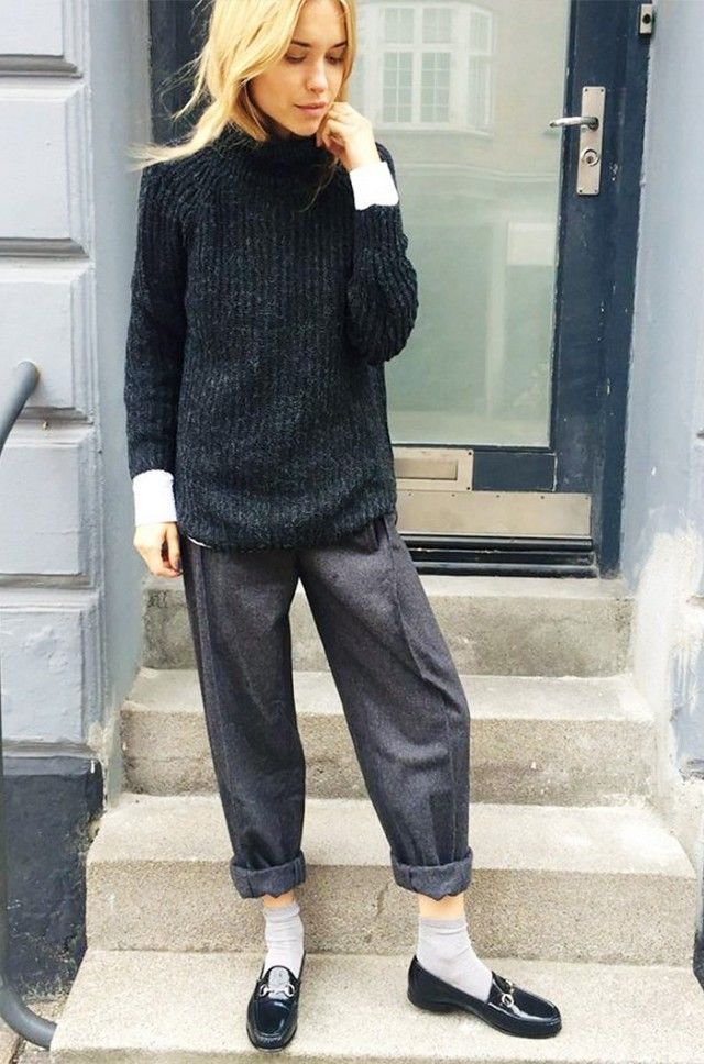 Pernille Teisbaek wears a white t-shirt layered underneath a ribbed turtleneck sweater with cuffed trousers, socks, and Gucci loafers
