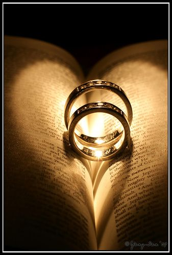 photo of wedding rings on a bible with a heart reflection