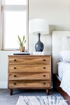 A natural wood, angular beside table with simple nightstand styling in Alice Lane's Modern Glass House. Shop the Diamond Chest in dark walnut on our website: https://alicelanehome.com/product/diamond-chest/