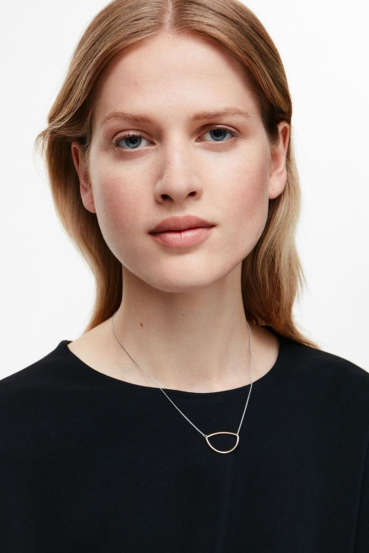 This necklace has a curved metal shape pendant, in contrasting metal, hanging from a classic fine chain and fastens with a simple clasp.