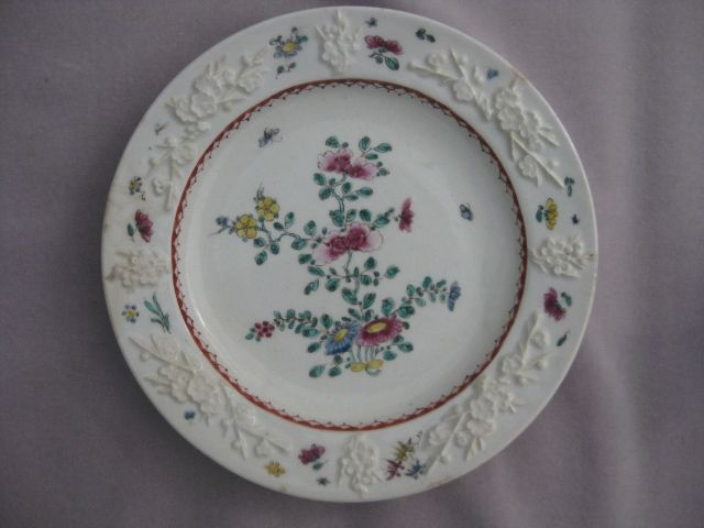 A Bow octagonal  plate with a moulded prunus border and decorated in the famille rose style with  a flowering  bush to the centre and further scattered flowers to the rim. Unmarked   Circa 1758 Diam. 9""