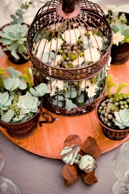 Hot Trend! Using bronze or white bird cages filled with flowers for centre piece…