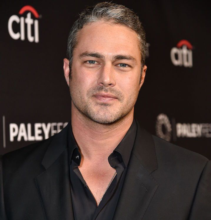 taylor kinney grayish hair wearing black tux and button up shirt close up in front of backdrop making serious face