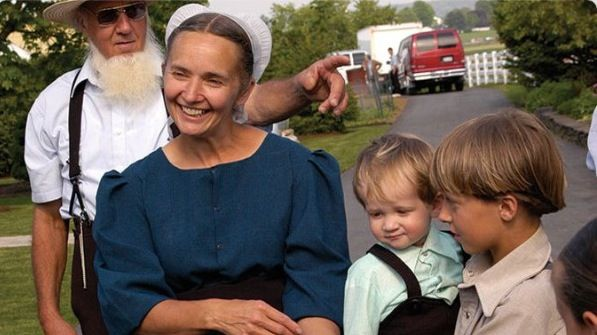 Smiling Amish woman and family.