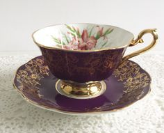 Vintage china tea cup and saucer made by Royal Albert in England. This duo has a purple ground with heavy gold chintz and gilding. Inside the