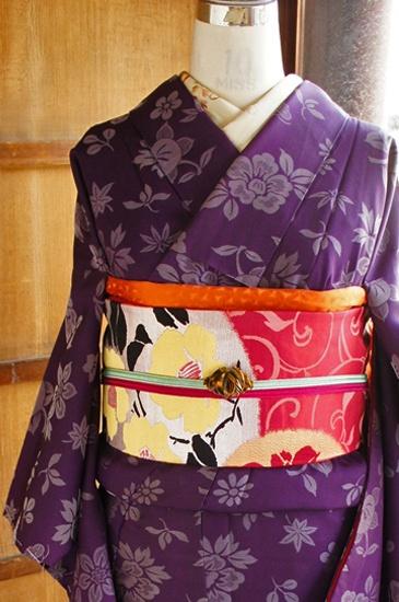 しっとりとしたツヤのある、ほのかに灰みがかかった深く美しい紫色の地に、光の加減や角度で美しく浮かび上がる、橘や鉄線、小菊や梅花、萩や松、桔梗や蔦葉が散り敷くように織り出された昭和レトロ・大正ロマンなムードただよう袷着物です。