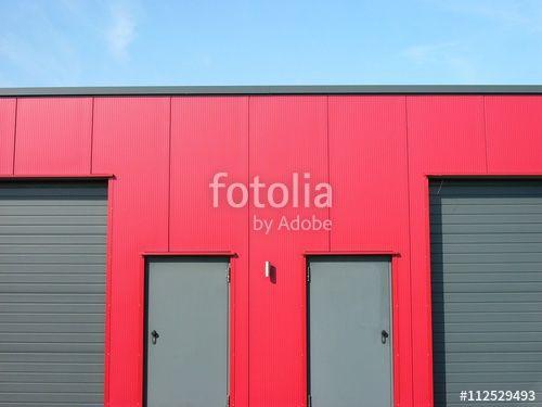 Moderne Lagerhalle mit roter Fassade und grauen Stahltüren und Rolltoren in Lage bei Detmold in Ostwestfalen-Lippe