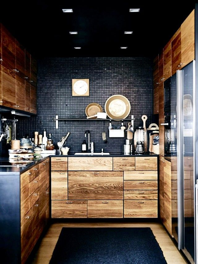 Industrial chic kitchen space with reclaimed wood cabinents and black backsplash
