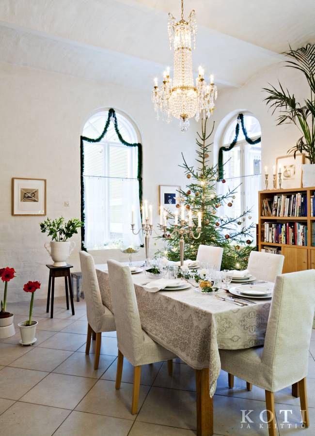 Salin kolmimetrset holvikaari-ikkunat ovat juhlavat. Aattona kristallikruunuun sytytetään kynttilät. Pellavaliina, kukat ja vanhat arabian astiat luovat jouluun juhlavaa tunnelmaa. Koti ja keittiö, kuva Kirsi-Marja Savola.