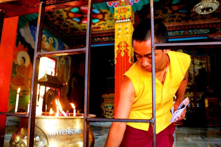 Tibetan monk lights candles inside the monastery before morning prayers.
