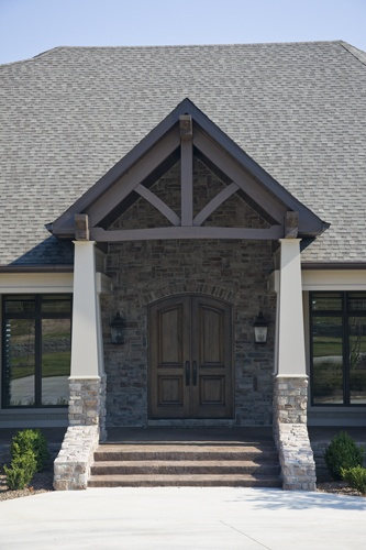 Rustic columns and cedar trusses are used on the front and for Rustic porch columns