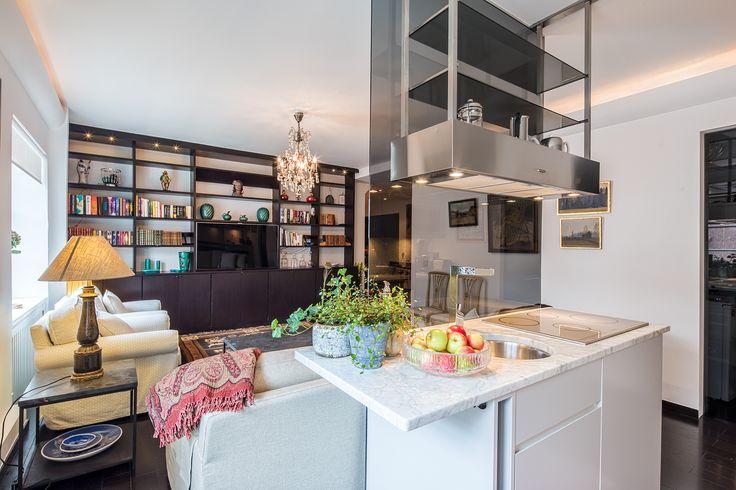 Vardagsrummet sett från köket. Rökfärgad glasvägg som delvis avskiljer mot vardagsrum - kök köksö