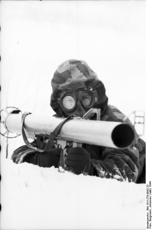 """Russia. German soldier with gas-mask and an antitank rocket launcher called """"Panzerschreck"""" or """"Ofenrohr"""" ( stove pipe). March 1944"""