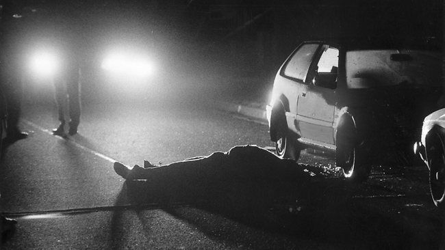 The body of Alfonso Muratore lies on the road outside his Storey Ave, Hampton home. A hooded gunman shot him as he left for the Footscray Fruit and vegetable market. Picture: HWT library.