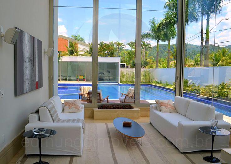 Próximo à porta de entrada, sob a suntuosa escada em mármore, a charmosa sala com lareira recebe os moradores especialmente nas noites mais frias, e oferece vista para a piscina e para a parte de trás da casa.