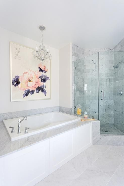 A large floral art piece hangs over a white wainscot bathtub fitted with a marble deck and a polished nickel hook and spout tub filler lit by a mini crystal chandelier.