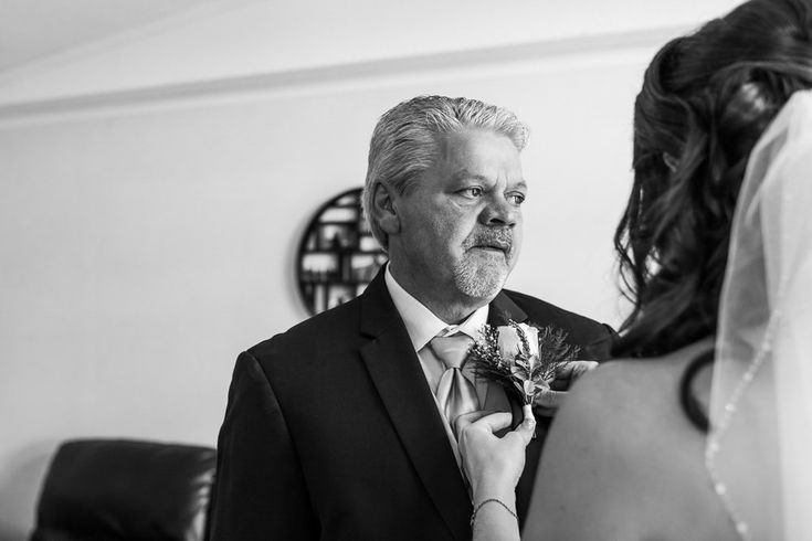 Bride helping her father in wearing corsage