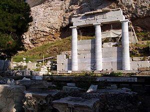 Santuario di Asclepio; V-IV secolo a.C.; tempio dorico; versante meridionale dell'acropoli. Si trattava di un luogo di culto e centro terapeutico, dove si riunivano insegnanti delle scuole mediche dell'epoca e in cui scorreva una sorgente sacra. Si consideri anche la fonte http://www.greciaturismo.net/atene/santuario-esculapio.php