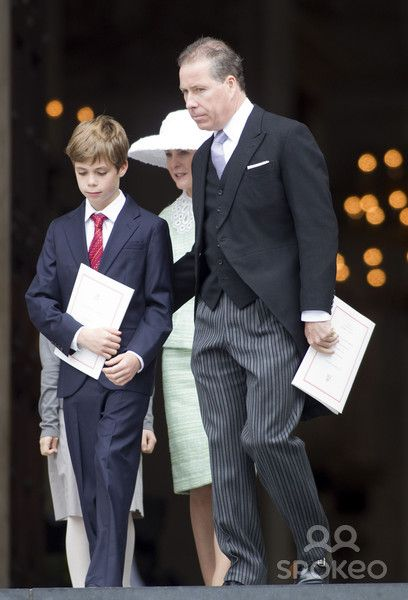 On the right is David Armstrong-Jones, Viscount Linley. He was born in 1961 to Princess Margaret, sister of the queen.  Therefore,  he is the nephew of the queen and first cousins with Prince Charles.  He is with his son Charles Armstrong-Jones, born in 1999, and who is second cousin to Prince William.  Behind them is Serena, Viscountess Linley.