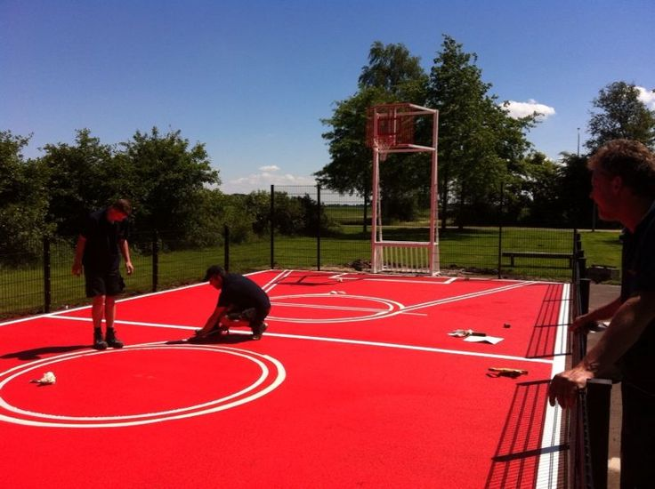 De rode coating en witte belijning zijn aangebracht, nu het afplakken voor de gele basketbal-lijnen.