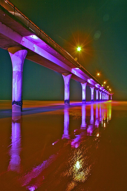 New Brighton Pier in Christchurch, New Zealand is illuminated at night and changes colours and has different lighting effects that make this a great spectacle