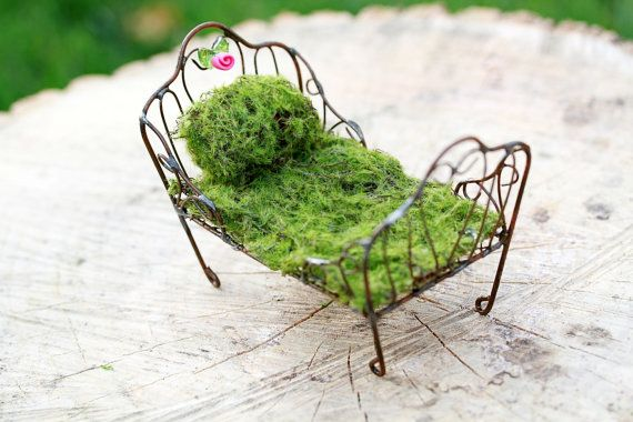 A sweet little rustic wire fairy bed. It comes complete with a coverlet made from artificial moss along with a pillow to match. The headboard