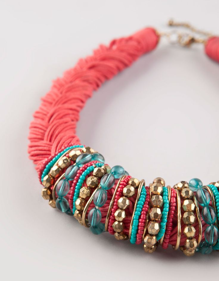 Coral braid and turquoise beads. Not crazy about the colors, but like the idea of winding loops around a braided necklace in the middle.