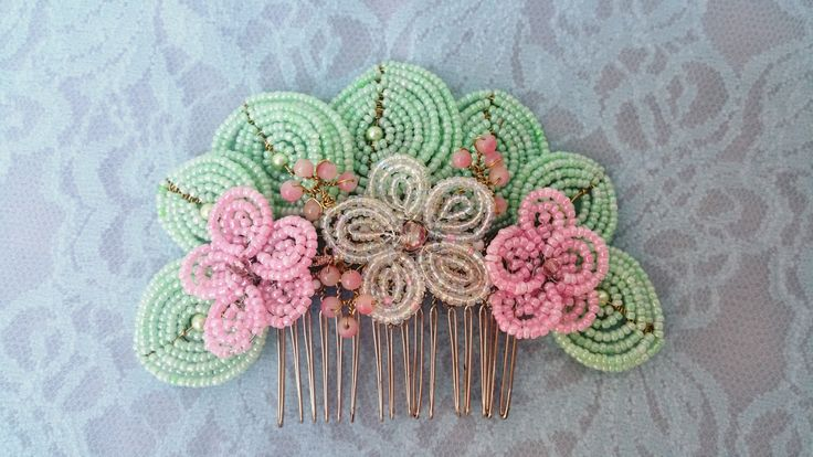 A hair comb featuring french beaded flowers and leaves, created by Annalee Beer of Aureate Resilience Designs.