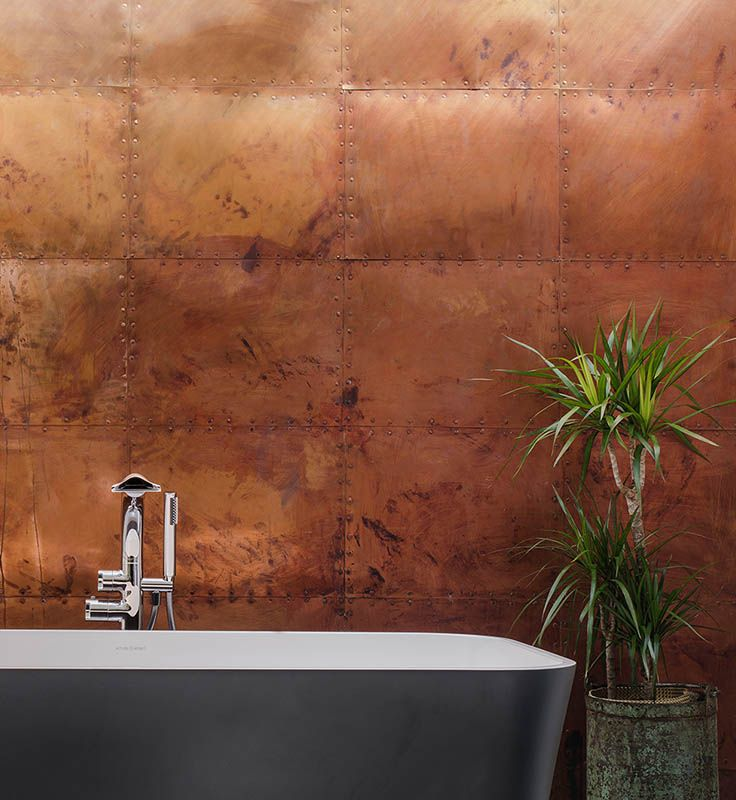 The Edge from Victoria + Albert Baths against a stunning copper wall.  Visit our website for more freestanding bath inspiration.