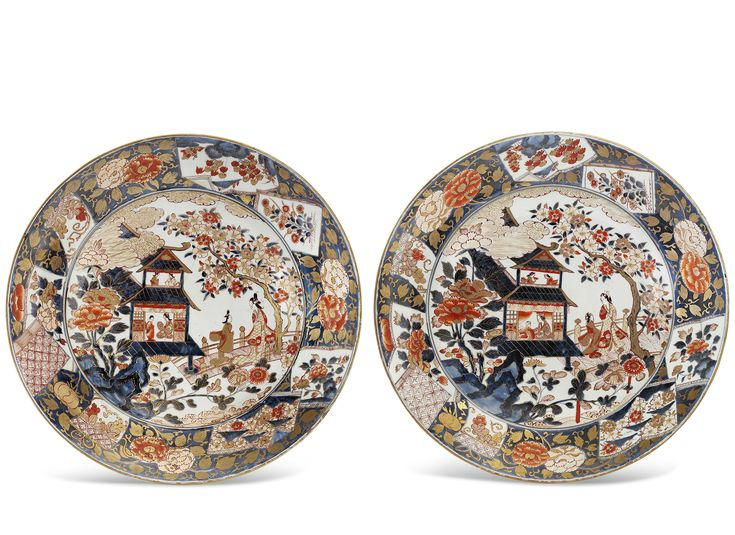 THE PROPERTY OF A GENTLEMAN OF TITLEA Pair of Fine and Rare Designed Imari ChargersEdo period (late 17th - early 18th century)Each decorated in iron-red and gilt on underglaze blue with a central roundel depicting a pavilion with a mother and a child boy behind the veranda and two ladies on the upper floor, in the garden a lady and her attendant in conversation on the bridge, surrounded by blossoming cherry, chrysanthemum and peony beneath clouds, the rim with open and closed books with…