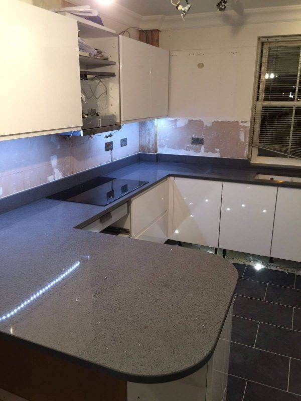 This white glossy kitchen features the Grigio Scuro Stella. It is a dark grey that has a sparkle running throughout. It is a perfect match against the white glossy cabinets and dark grey tiling on the floor.