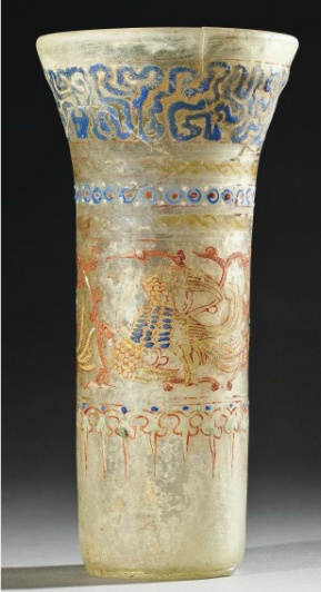 A MAMLUK ENAMELLED GLASS BEAKER   SYRIA, SECOND HALF 13TH CENTURY   Of cylindrical form widening to the vertical mouth, the sides with a band of three flying mythical birds, a band of gilt and blue enamel water motifs around the mouth
