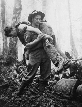 """Corporal Leslie """"Bull"""" Allen carrying an American casualty down the slopes of Mt Tambu 30th July 1943.....During the American Assult against the Japanese on the mountain 50 American soldiers were injured. ... Bull who was not suppose to be involved but witnessing the casualties involved himself... Facing snipers, machine gun and mortar fire carried service men one at a time down the rough terrain of Mt Tambu....  Allen saved between 12 and 18 men that day."""