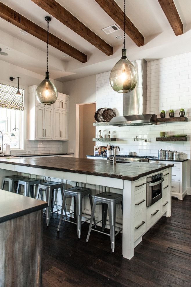 Kitchen with dark wood floors, exposed wood ceiling beams, large island with wood countertop, white cabinets, pendant lighting   Schroeder