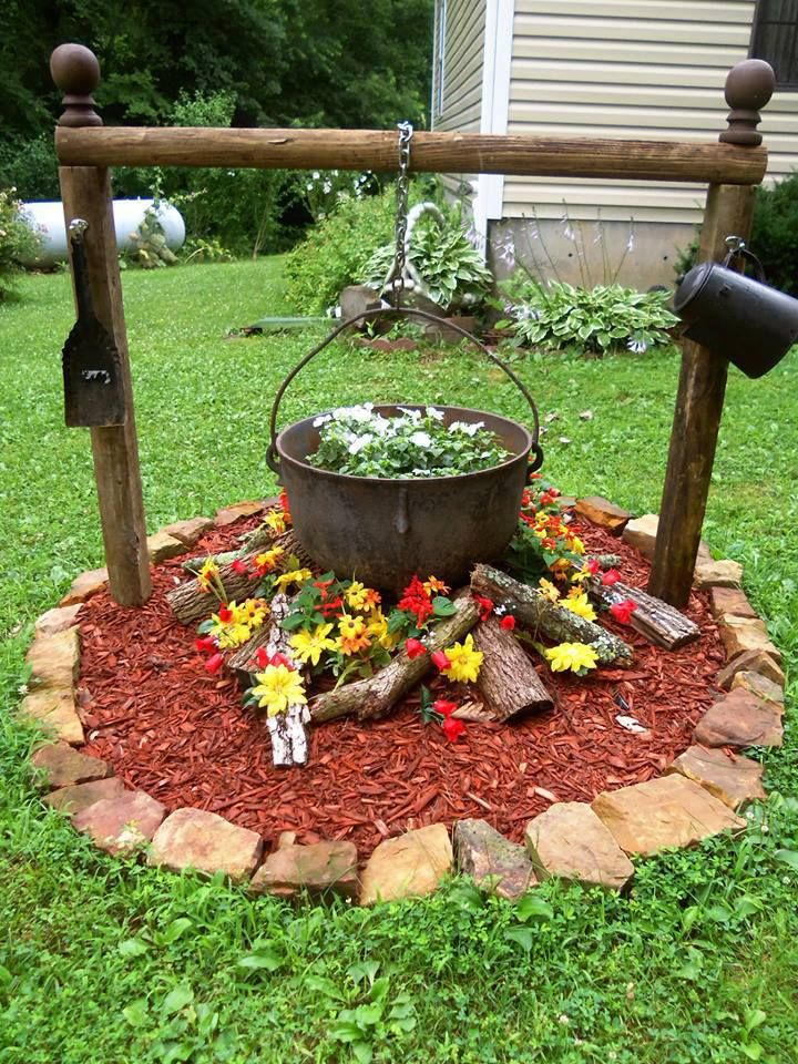 Iron kettle used as planter. I like the logs added in this one but planting the red salvia I've seen with the other hanging kettle. Great idea for a small accent garden.