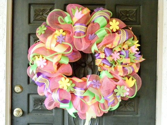 """Easter Wreath.  I made this wreath with coral deco or geo poly mesh and glittery sparkling spring flowers. I added a fabulous assortment of pastel spring ribbons and lome green sparkle tubing. This wreath is super whimsical and fun!    Wreath measures approximately 28"""" accross."""