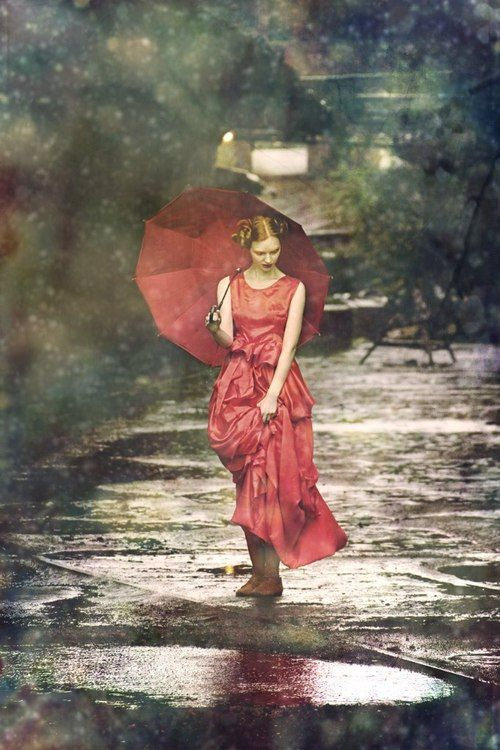 woman with umbrella in red dress under the rain