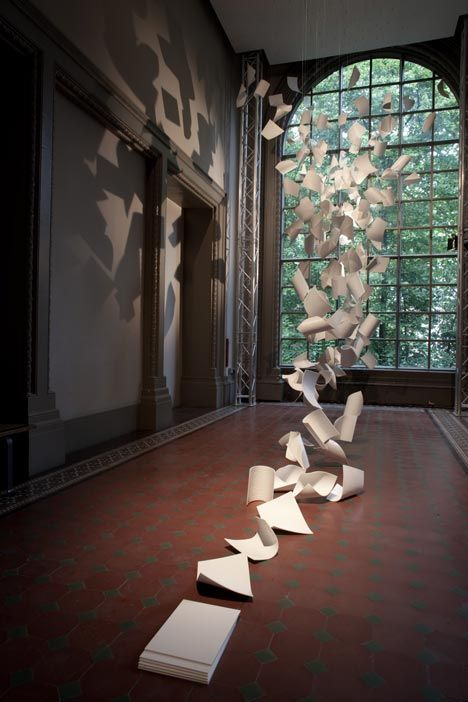 """Installation by Paul Cocksedge at the V & A for London Design Festival - """"Gust of wind"""". The sheets are given away during the festival, hard material that can be used as paper trays."""