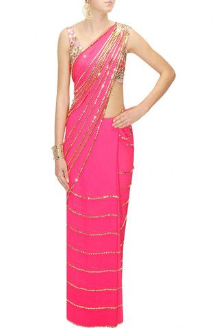 This pink georgette sari is embellished with gold beads and embroidered panels. This sari is is paired with pink mirror and zari embroidered blouse in net with shantoon silk underlining.