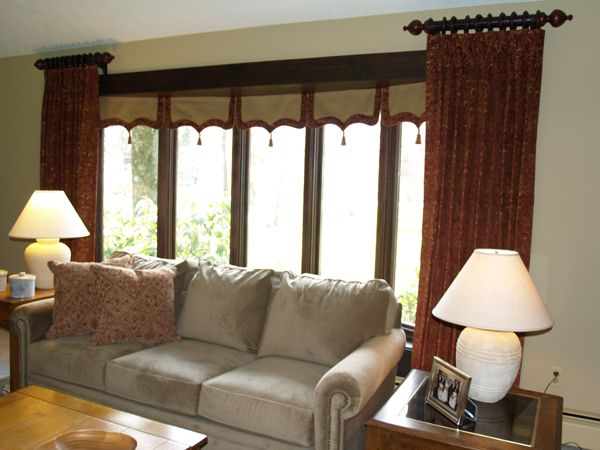 This window is called a bow, rather than a bay because it gently curves rather than having straight angular lines. The customer has honeycomb shades in each of the five windows so we created a simple valance to cover the headrails when they are raised. The side panels are hung from two short rods rather than one long rod with a bracket showing in the middle. (One of my pet peeves!). Contact us for a free in-home consultation http://dressedwindows.com/ (440) 498-9119.