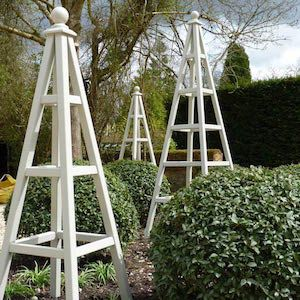 Set of 3 wooden garden obelisks painted Hardwick White set in border by garden designer Sarah Plested