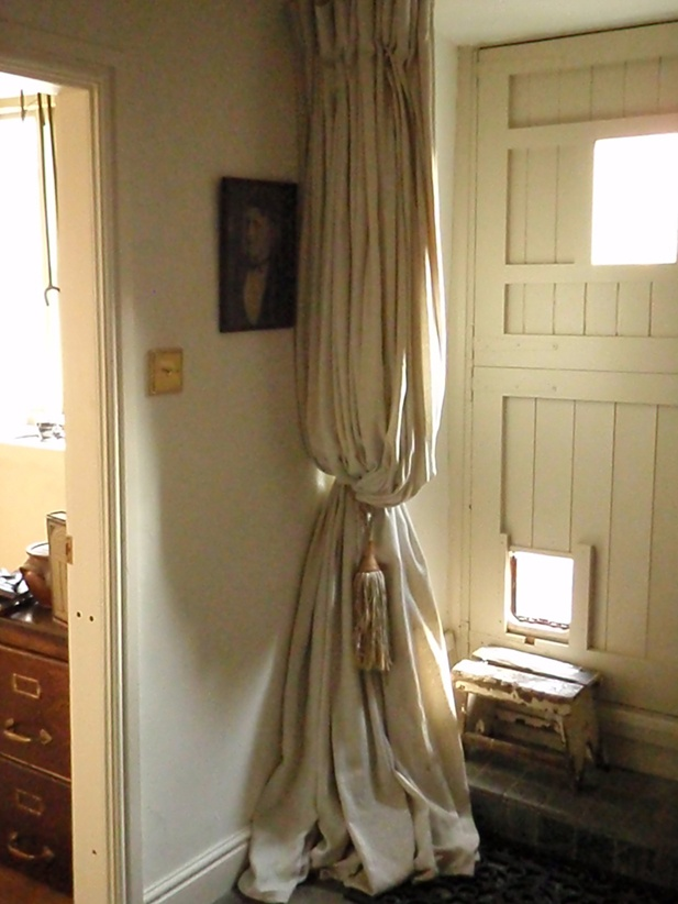 """Curtains made from """"painter's dust cloth,"""" probably the English equivalent of a drop cloth. Lined with flannel to block winter gales. Clever girl!"""