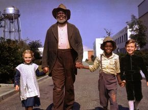 behind the scenes of Song of the South - James Baskett (Uncle Remus) leading Driscoll, Patten and Glenn Leedy through Disney's backlot