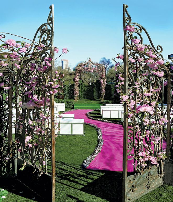 The pretty, hot pink curved aisleway and aisle runner looks especially nice with the pink floral-accented, iron gates at the ceremony location.