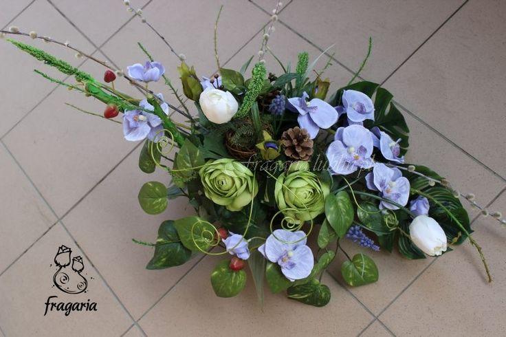 Wiosennie… ale bez standardowej żółci. Kompozycja stonowana, naturalne dodatki, lekki błękit w połączeniu z ciemną zielenią i seledynem. Akcenty wiosenne to białe tulipany i bazie.