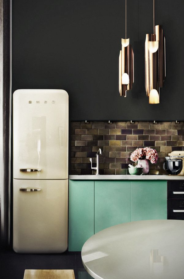 A small kitchen with black walls and floors, a dark tiled backsplash, an adorable Smeg refrigerator, and two Galliano Suspension Lights is brought to life with a series of fresh pale green lower cabinets. Lighting by DelightFULL.