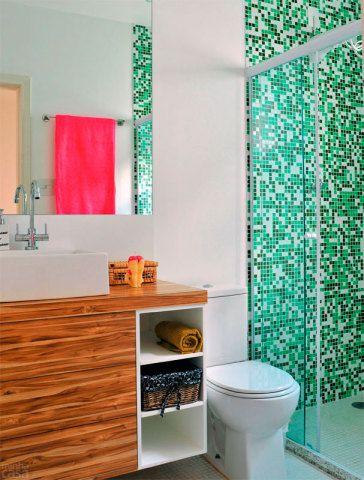 As paredes do banheiro da designer de interiores Ana Maria Mouawad expõem tinta epóxi branca e pastilhas de vidro em vários tons de verde na área de banho. Um grande espelho sem moldura foi fixado na superfície acima da pia com uma cola apropriada ao material.