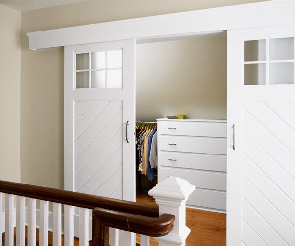 barnstyle sliding doors close off a walkin closet outfitted with built